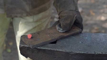 hot rod : slow motion of blacksmith makes nail head on red-hot bar on anvil in outdoor rural smithy