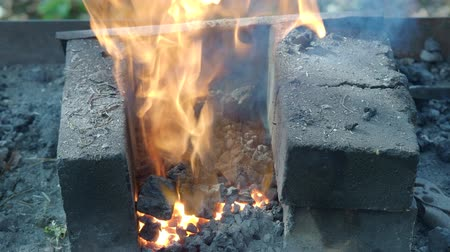 firebox : village blacksmith puts the iron workpiece in burning coals for heating Stock Footage