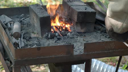 heating up metal : village blacksmith heated the iron rod in burning coals in forge before forging in rural smithy