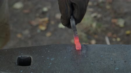 hot rod : village smith forges red-hot workpiece on anvil in outdoor rural smithy to make a nail