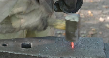 hot rod : blacksmith forges red-hot bar on anvil in outdoor rural smithy to make a nail