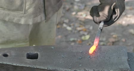 aglow : blacksmith forges glowing bar on anvil in outdoor rural smithy to make a nail Stock Footage