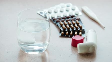 medical thermometer : glass of water with effervescent tablet and various medications on a pink stone board