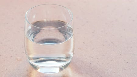 cold drinks : glass of pure water on a pink stone board