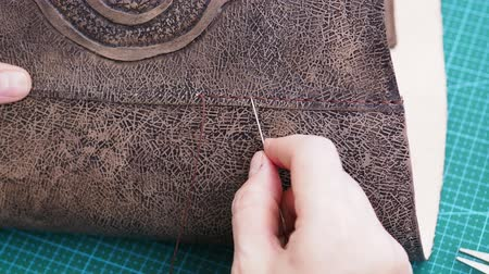 workshop bag making the carved leather bag - craftsman sews the flap to the leather handbag Стоковые видеозаписи
