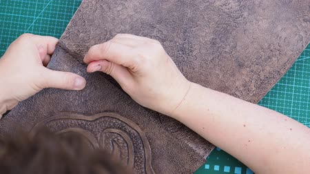 craftsmanship making the carved leather bag - craftsman?s stitches the leather handbag