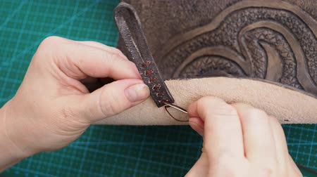 tutturma : workshop bag making leather bag - craftsman sews loop for fastening handbag