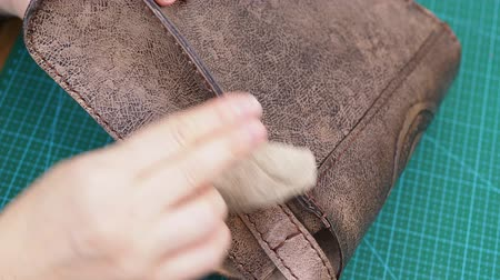 craftsmanship making the carved leather bag - craftsman polishes the handbag with wax Стоковые видеозаписи