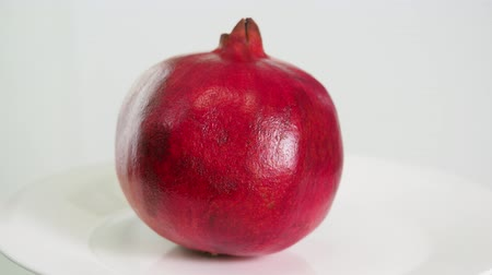 red pomegranate fruit on white plate close up on white background