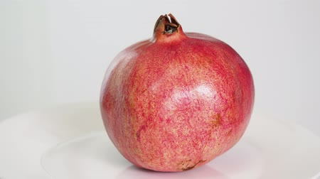 close up on white background whole ripe pink pomegranate fruit Стоковые видеозаписи