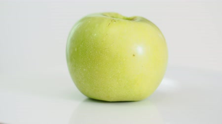 bitten yellow green apple on white plate