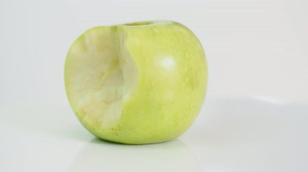 bitten yellow green apple on white plate on white background, part 1