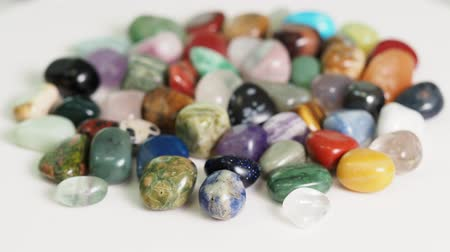 handful of various tumbled gemstones rotating on white table close up Стоковые видеозаписи