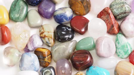 view of various tumbled gemstones rotating on white table close up