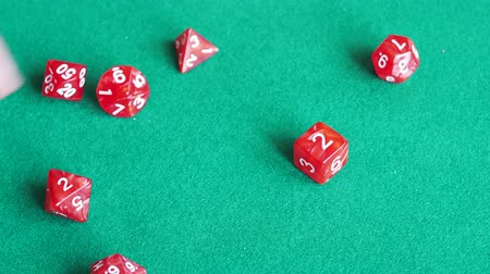 player throws two dies of red dungeons & dragons board game on green baize gaming table close up