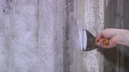 шпатель : The man plasters openings in a wall.