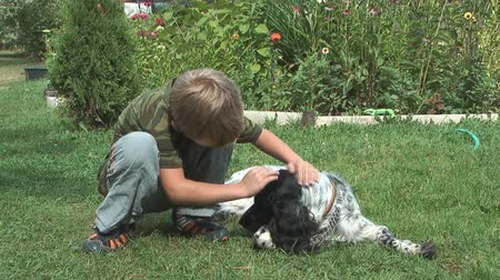itaatkâr : A child stroking a dog lying on the grass.