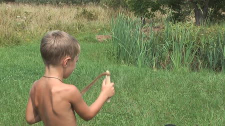 travessura : Boy shoots from a wooden slingshot summer day. Vídeos