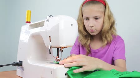 ziguezague : A teenage girl sews braid to the edge of a piece of cloth