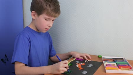 plastelíny : The schoolboy makes a plasticine application on a sheet of cardboard Dostupné videozáznamy