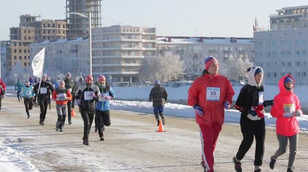 extreme weather : Runners in various sports and masquerade costumes run at different speeds on the street Naberezhnaya Tukhachevskogo