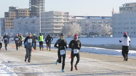 extreme weather : Runners run along the embankment of the river om on a cold winter afternoon