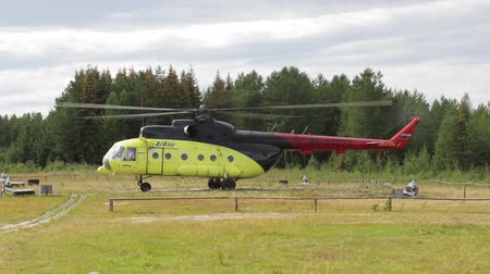 mi : Passenger helicopter takes off from the field helipad in taiga Siberian village