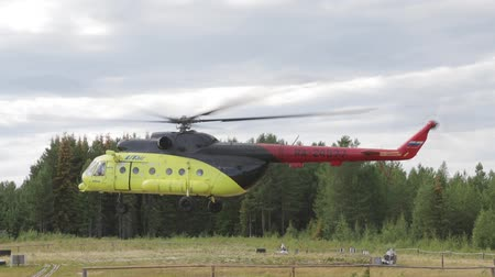 mi : Passenger helicopter takes off from the field helipad in taiga Siberian village.The effect of the presence of the camera shaking caused by an air wave Stock Footage