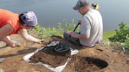 opencast : Two archaeologists are looking for small metal objects in the scattered soil with the help of a metal detector Stock Footage