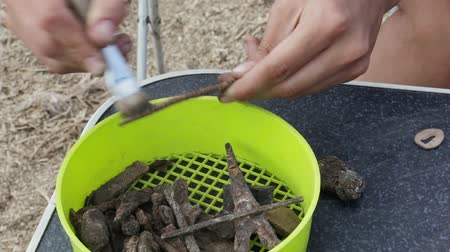 копье : The work of the archaeologist on manual primary cleaning of the find - a rusty arrowhead