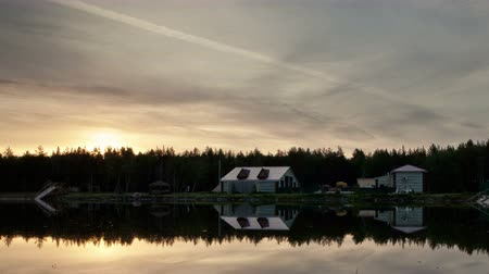 tin roofs : Houses on the edge of the forest. Pond. Sunset. Trace of aircraft in the sky.