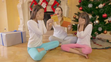 мама : Two cute girls in pajamas receiving Christmas gift from mother at morning