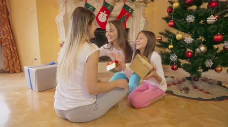 beijos : Two girls receiving Christmas gifts from mother at morning
