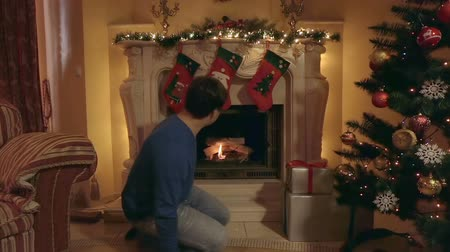 faház : Young man inflaming fire in fireplace at living room decorated for Christmas