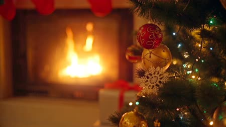деревья : Background with colorful baubles on Christmas tree next to burning fireplace at living room