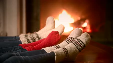 sock : Closeup shot of mother, father and a child in woolen socks warming at the fireplace Stock Footage