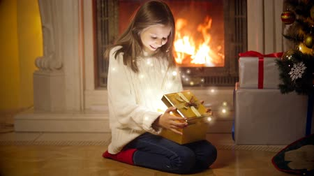 hediyeler : Cute girl in sweater opening magical Christmas gift box. Light and sparkles flying out of the box Stok Video