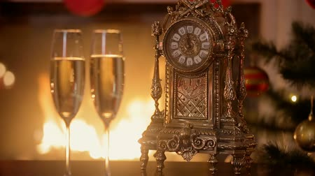 faház : Closeup of two glasses of champagne next to old clock counting minutes to the New Year on table next to burning fireplace Stock mozgókép