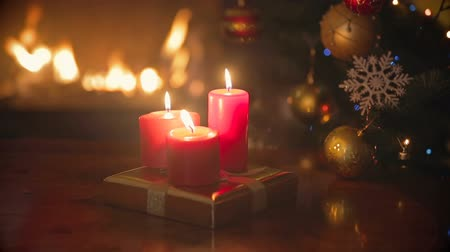 şömine : Three burning red Christmas candles on dinner table at living room next to fireplace and Christmas tree Stok Video