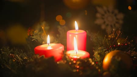 мерцание : Closeup of Christmas wreath with three burning red candles. Blurred glowing colored lights on background