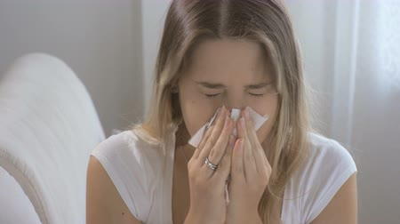 alergia : Young sick woman sitting up on sofa at living room and sneezing paper handkerchief Wideo