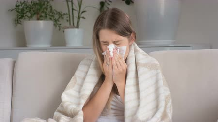 nariz : Young sick woman covering in blanket suffering from flu and blowing nose in paper tissue