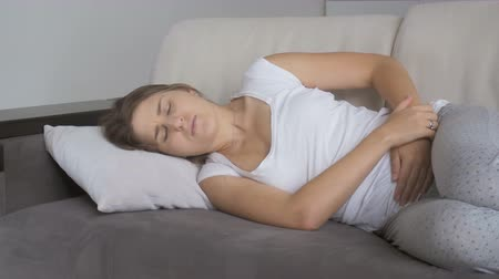 żołądek : Young woman suffering from stomach ache lying on sofa at living room