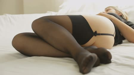 spodní prádlo : Pan shot of sexy young woman in black stocking and lace lingerie lying on bed in front of big window Dostupné videozáznamy