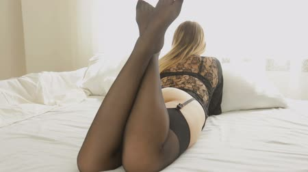 külotlu çorap : Sexy young woman in black lingerie and stocking relaxing on big bed at window Stok Video
