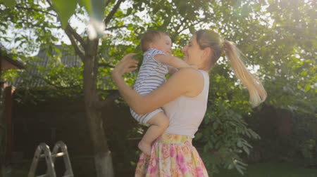sarılmak : Cheerful young mother with baby standing under tree at sunny day Stok Video