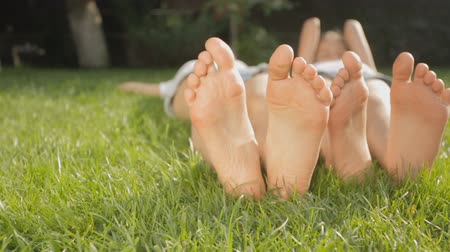 ayak parmakları : Dolly shot of two girls feet relaxing on grass at sunny day