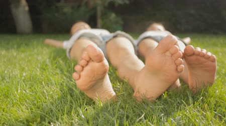 yards : Dolly shot of two friends feet lying on grass at park