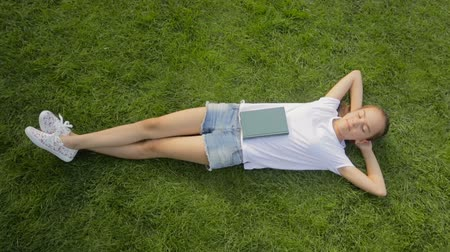 enciclopédia : Beautiful yong girl relaxing on green grass at park with book