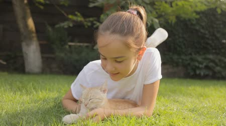 lefekvés : Dolly shot of smiling girl relaxing on grass and caressing red kitten Stock mozgókép